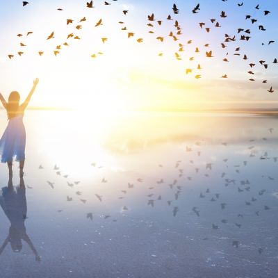 woman standing on the beach in the water arms to the sky birds overhead and reflected in the water