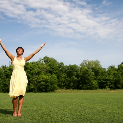 "A black woman with short hair is standing in a field, wearing a sleeveless, yellow, knee length dress with her arms stretched out over her head in a ""v"""""