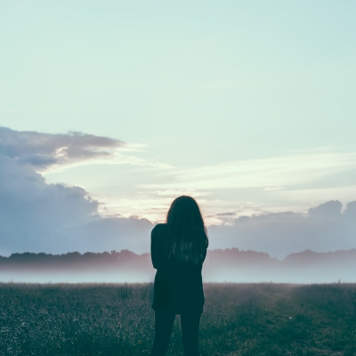 person shown from behind in field with clouds and bluish sky
