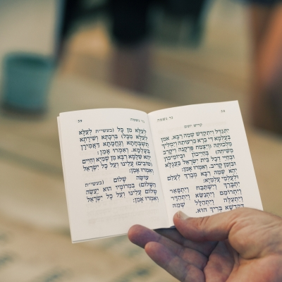 hand holding prayerbook opened to kaddish