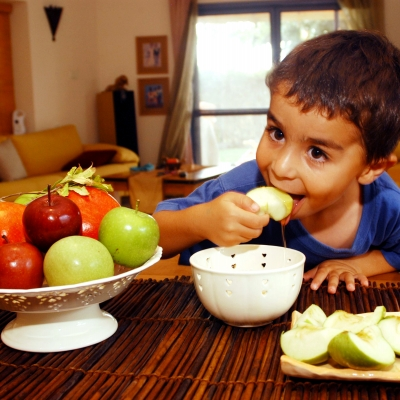 child eating apple dipped in honey next to bowl of apples