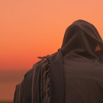 orange sky with person wearing a tallit covering their head shown from behind