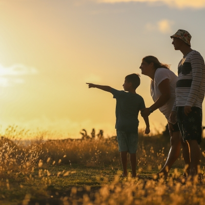 young boy with adult woman and man in sunlit field. boy is pointing into the distance and adults are looking in that direction.
