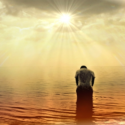 man kneeling in the ocean under sunlight