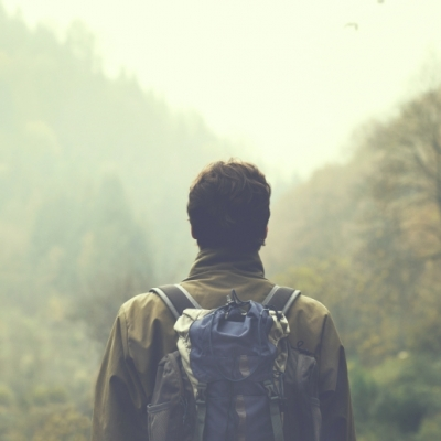 man hiking with backpack in woods