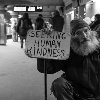 """a black and white portrait with an unhoused man with a long beard holding a sign that says """"SEEKING HUMAN KINDNESS"""" in black letters"""