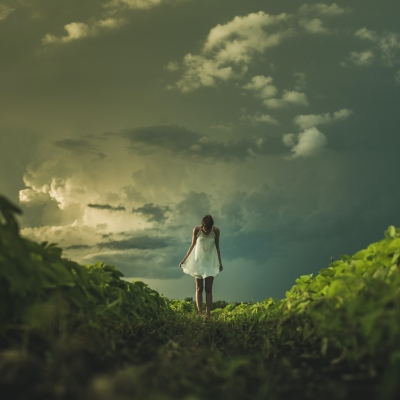 woman shown from far away in white dress looking down, standing on green grass with dark sky and clouds overhead