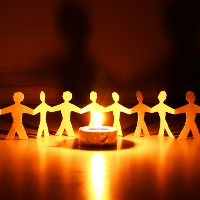 a cut paper chain of people stands in the background of a lit tea light and the flame illuminates the paper chain