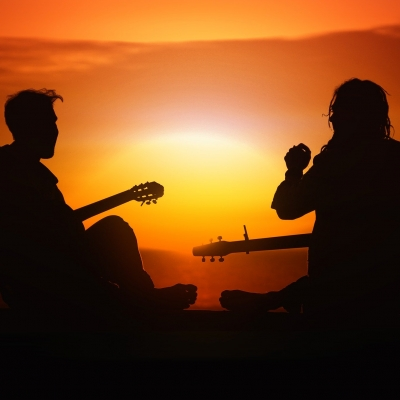 silouhette of two people playing guitar against sunset