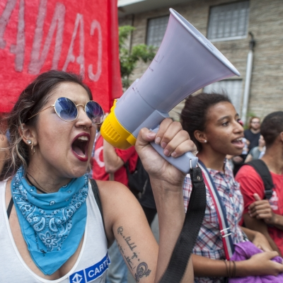 A protestor is pictured marching in a large crowd. They have long hair pulled back, sunglasses on their face, a blue bandana tied around their neck and are shouting into a megaphone. Additional protestors can be seen next to them.