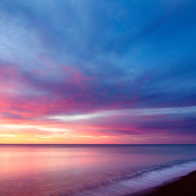 multi-colored sky from blue to pink to yellow over smooth ocean surface