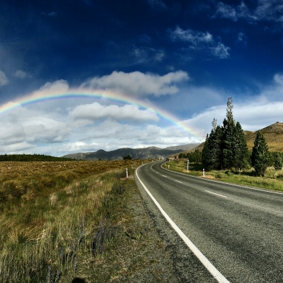 We see a landscape photo with a curved, paved highway road on the right hand side and a field to the left. The sky is a deep blue with fluffy white clouds and off in the distance there is a full rainbow