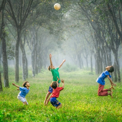 four children are playing in a field surrounded by trees. The one on the far left is wearing a blue shirt and white shorts and is getting ready to jump. The one in the middle back is wearing a green shirt and blue shorts and is jumping in the air with both hands overhead. The one in the middle front is wearing a red shirt and dark blue shorts and is squatting with both hands in the air, elbows bent. The fourth one on the far right is wearing a blue shirt and red pants and is jumping in the air.