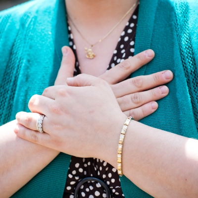A white person is pictured from the neck to the bottom of the chest resting their hands over their heart. They are wearing a black shirt with white spots under a teal cardigan and have a gold necklace, bracelet, and diamond ring on their ring finger.
