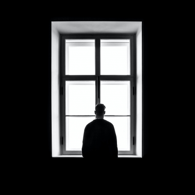black and white photo white window in center with black frame and man shown from behind standing in the center looking out the window