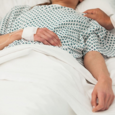 person on their sick bed in the hospital. IV attached to hand. hand of a doctor in white coat is on the person's shoulder.