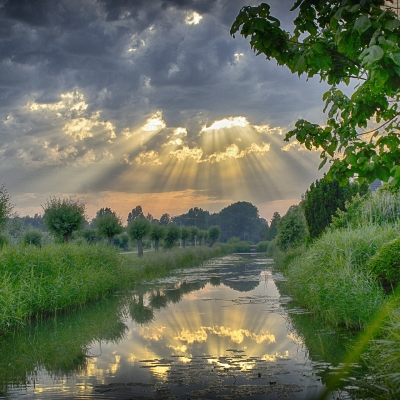 sun shining through clouds on river trees grass