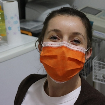 A light skinned person with long brown hair pulled back into a pony tail is wearing an orange surgical mask. In the background we see doctor's office equipment.