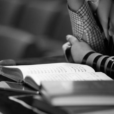 young person's arm wrapped in tefillin leaning over prayerbook