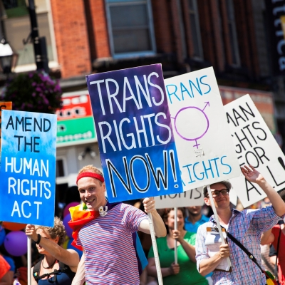 protest with signs reading trans rights now, amend human rights act