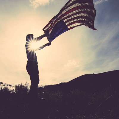 a person stands in a field holding an american flag in both hands waving it in the wind. The sun is peering through their two arms.