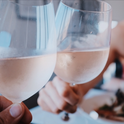 two wine glasses filled with white wine are being held by two people not pictured in a cheers motion