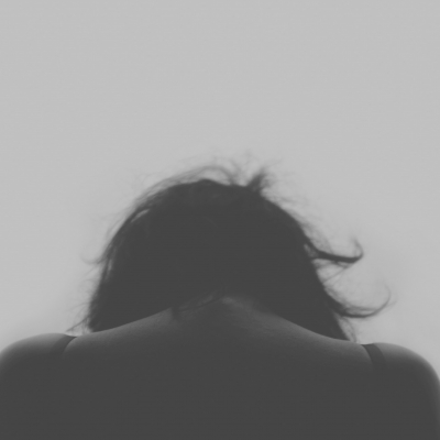 black and white photo of woman's head bent over shown from behind, dark hair against white background