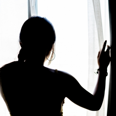silhouette of woman looking out window
