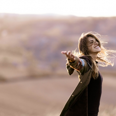woman filled with joy smiling and arms wide open