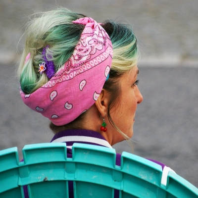 older woman sitting in bright turquoise chair outside. Head turned to the right. Her hair is dyed blue and bleach blonde and pulled back in pink handkerchief.