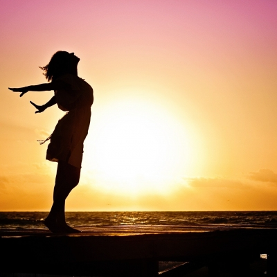 woman in silouette in front of sun and sea with arms spread wide behind her and lifting her face to the sky