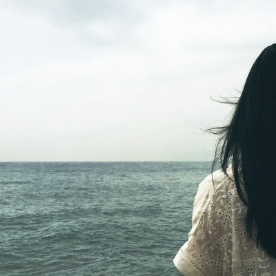 woman with long straight dark hair shown from behind facing ocean
