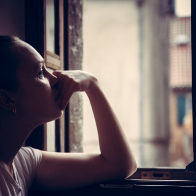 woman looking out window contemplating or sad