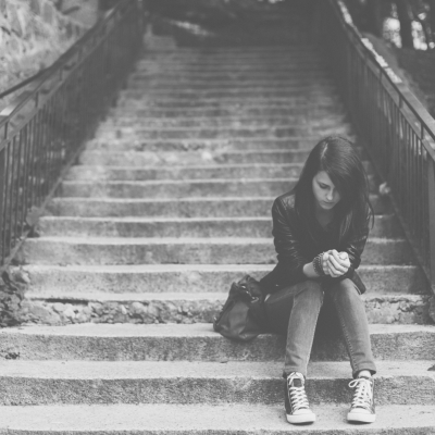 black and white photo of teenage girl sitting on steps looking down at her hands