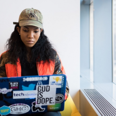 "A black woman with long dark hair is sitting on a yellow chair with their laptop on their lap. They are very focused on the screen. On the laptop are several stickers, including one thats says ""God is hope""."