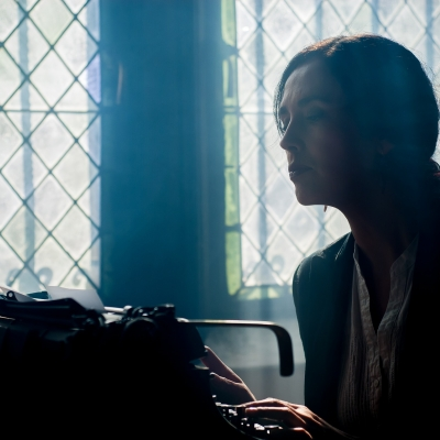 Person with long hair pulled back into a low bun, sitting at a type writer typing. In the background are two stained glass windows with light streaming through.