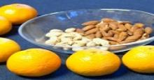 oranges surrounding a bowl of nuts
