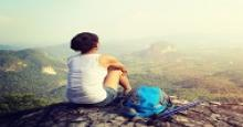 woman sitting on cliff after a hike looking at the view