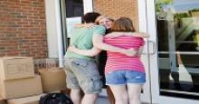 family members hugging someone in front of a door with lots of boxes