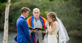 Rabbi Malka drinking water under the chuppah with partner and officiant