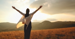 Woman in shawl facing sunset arms spread in the air