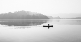 lone boat on a body of water, black and white photo