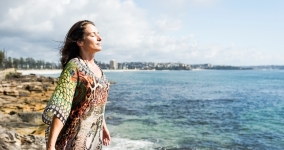 Woman with eyes closed breathing by the ocean