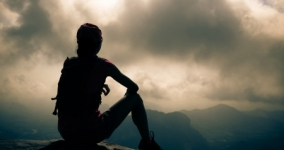 person in silouette sitting on mountain looking at gray clouds
