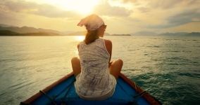 Woman facing sunset in boat