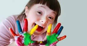 Girl with downs syndrome smiling with painted hands
