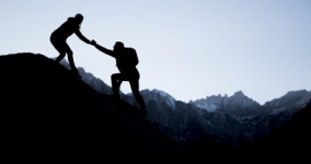 silouette of backpacker climbing mountain reaching up and someone holds their hand and helps them climb