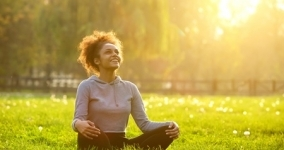 woman sitting in meditation post smiling in a field