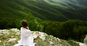 woman wrapped in white cloth sitting on edge of mountain