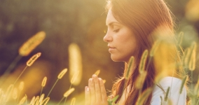 Woman with eyes closed and hands in prayer position in a field